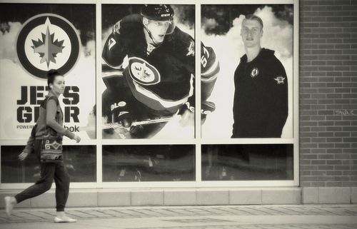 Lady walking past Winnipeg Jets store